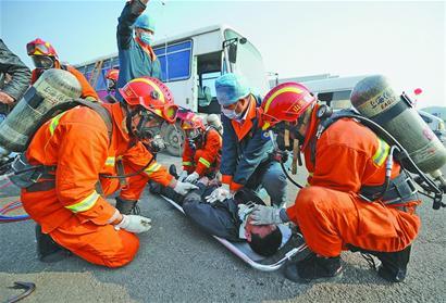 """昨天,在消防应急救援演练中,消防队员与医护人员一起""""抢救""""伤员"""